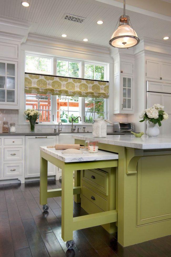 Кухонные занавески «кафе» из натурального материала с цветочным принтом. Цвет принта повторяется на фасаде кухонного острова, а тематика принта дополняется живыми цветами в интерьере