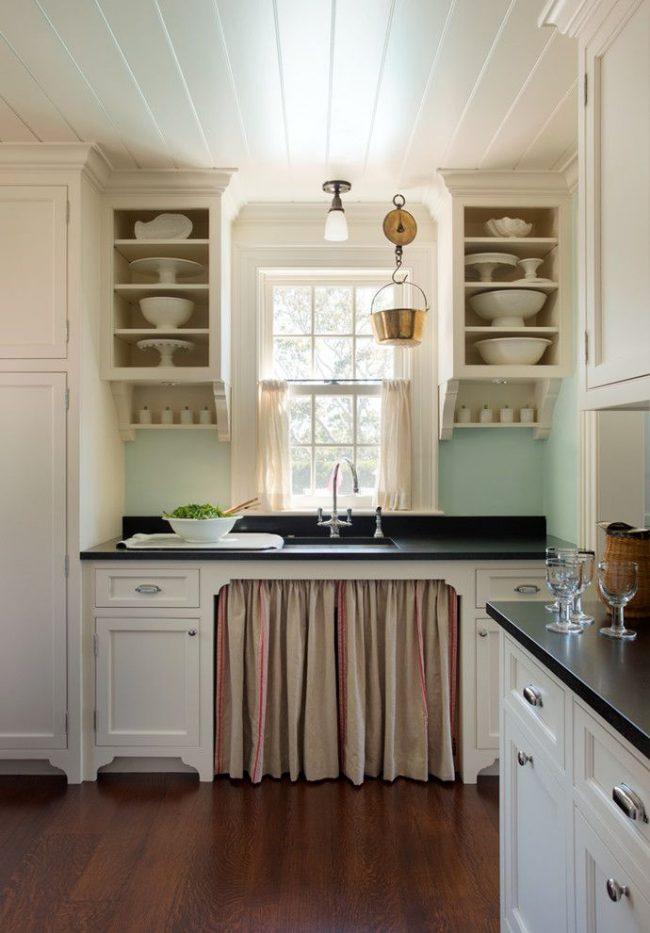 Кухня в пляжном стиле со свойственной цветовой палитрой: нежно-голубой кухонный фартук, белые фасады гарнитура, укороченные светло-песочные шторы на окнах и т.д.