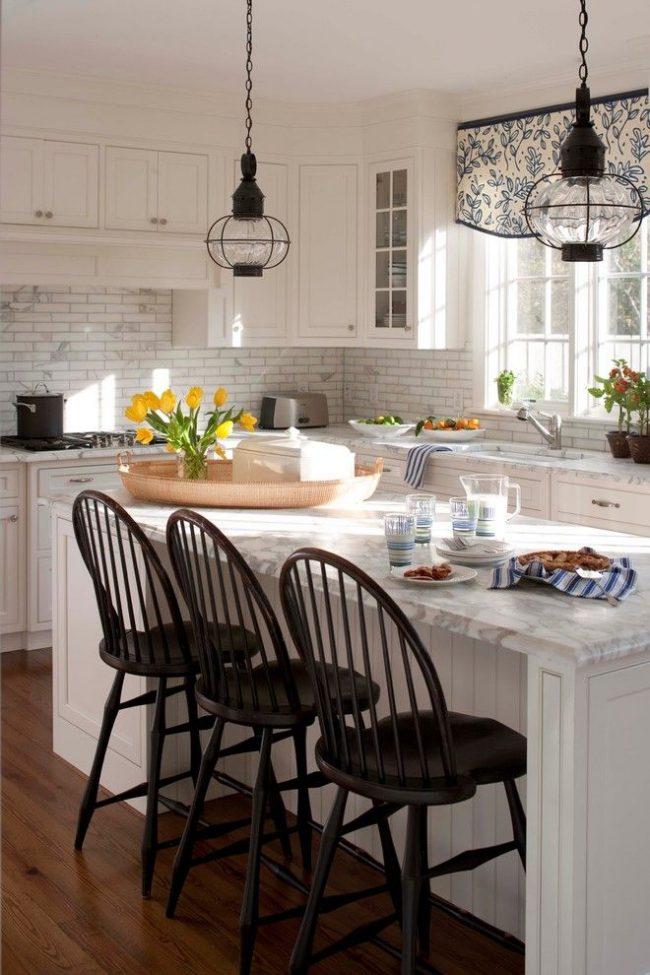 Короткие шторы для кухни в качестве акцента, выделяющегося простым растительным орнаментом, созвучным с обилием живых цветов на поверхностях, рабочей и обеденной