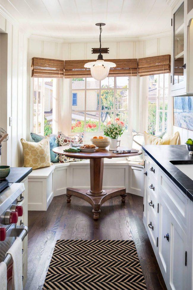 Круглый столик из дерева и угловой диван - отличное сочетание на маленькой кухне