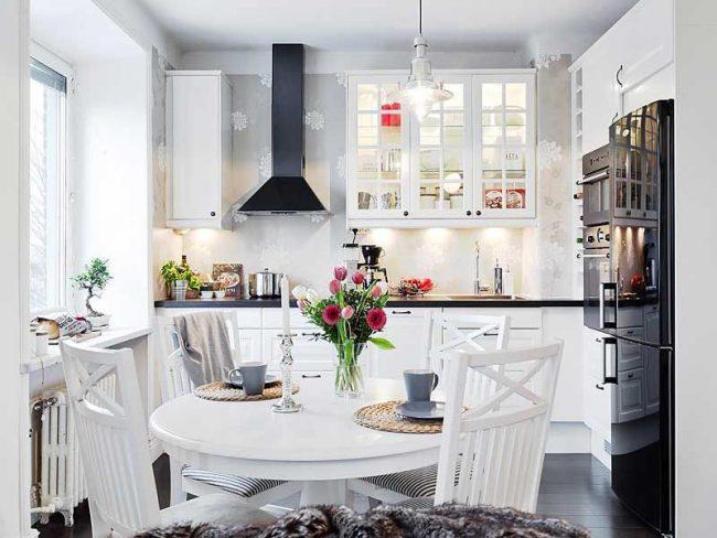 Круглый белый столик из дерева на маленькой кухне