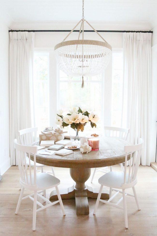 Круглый столик из ореха в интерьере светлой гостиной