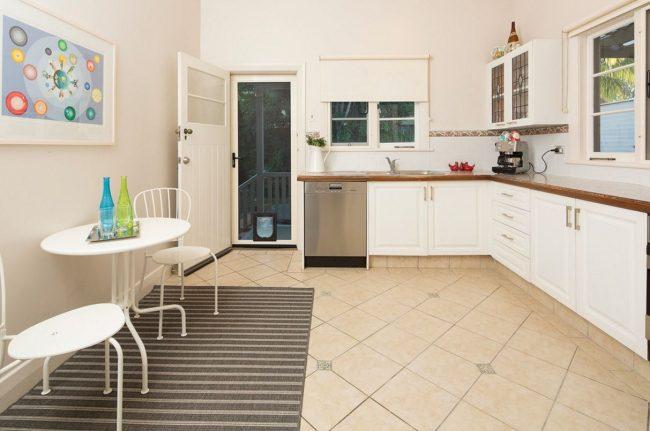 Бюджетный вариант кухни арт-деко: картины и бутылки в интерьере, полосатый коврик и белый кухонный гарнитур
