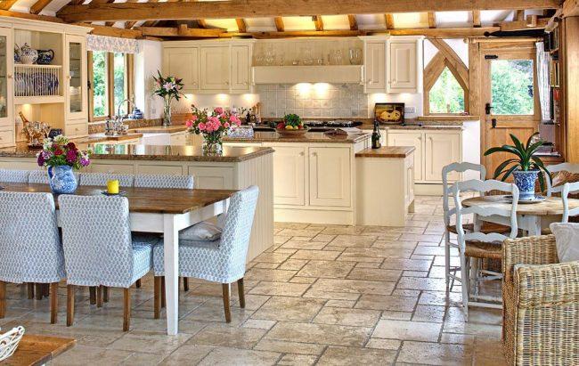 Винтажная мебель светлых оттенков, стулья с цветочной обшивкой и яркая посуда на кухне шебби-шик