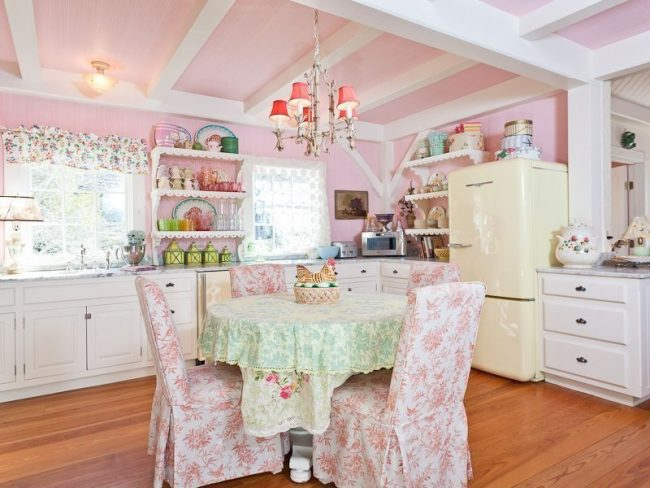 Кухня в стиле шебби-шик: розовая отделка стен и потолка, люстра, цветастые чехлы на стульях и бежевый кухонный гарнитур