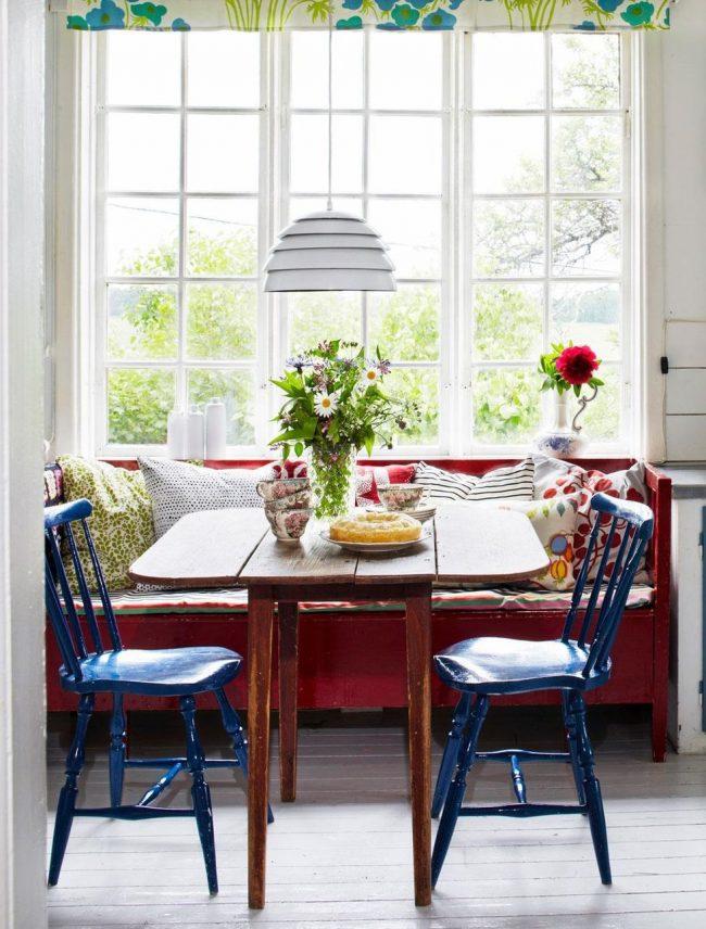 Эклектическая кухня с компактным раскладным столом-книжкой из натурального окрашенного дерева с эффектом состаривания и синими стульями того же эффекта