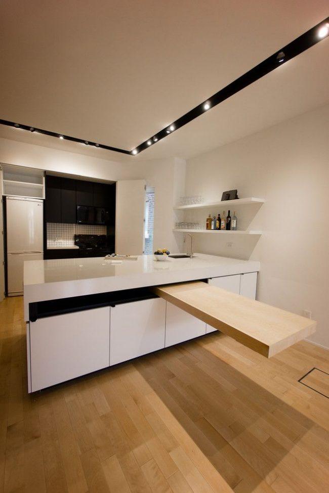 Выдвижной стол из кухонного острова на кухне в стиле минимализм