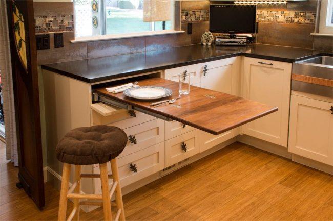 Кухонный гарнитур оснащенный выдвижным столом, который можно использовать не только как обеденное место, а и как рабочее