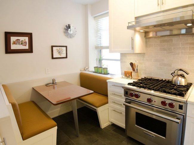 Современная малогабаритная кухня с компактным раскладным столом и удобными вместительными диванчиками