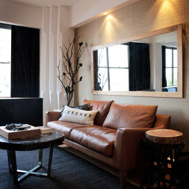 Коричневые диваны с кожаной оббивкой считаются своеобразной классикой для гостиной комнаты
