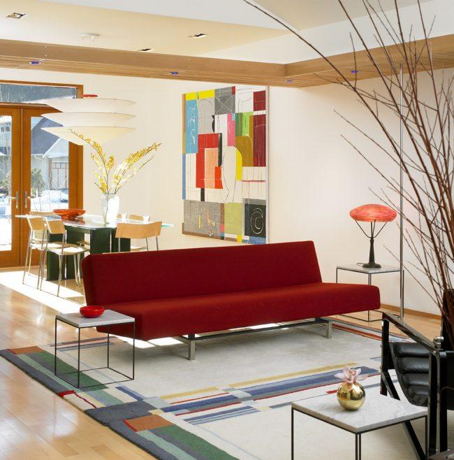 Интересным дизайнерским решением станет красный диван в интерьере вашей гостиной комнаты, поскольку такие диваны позволяют создавать нестандартные и смелые стилистические решения