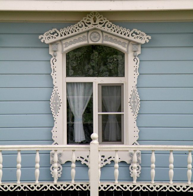 Пластиковый белый наличник на металлопластиковых окнах современного деревянного дома
