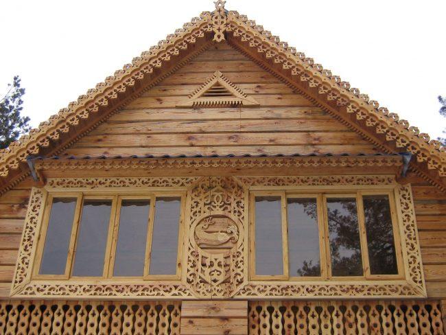 Деревянный дом с наличниками с растительными элементами