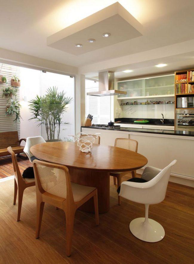 Овальный стол на кухне гостиной разделяет зону приготовления пищи и отдыха