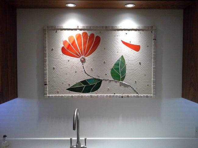 Небольшое мозаичное панно со стилизованным ярким цветком на современной кухнемозаичное панно с ярким цветком на современной кухне
