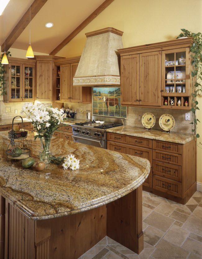 Еще один образец стиля кантри на кухне. Для панно над варочной поверхностью здесь выбран летний сюжет с коровой на пастбище