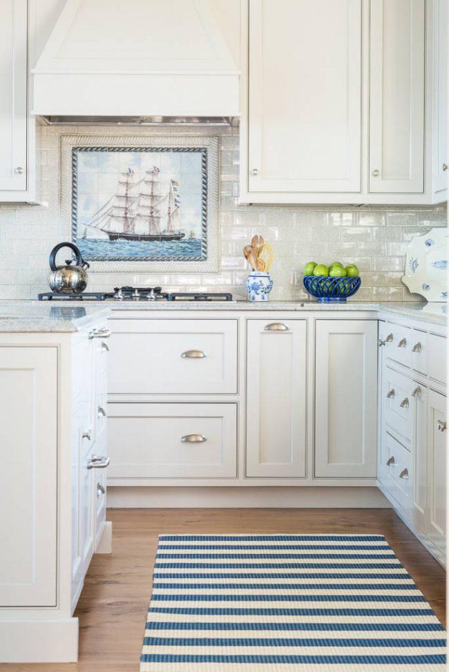 Традиционная белая кухня, в качестве очаровательного акцента в которой - романтичный морской сюжет на плиточном панно. На таких быстроходных клиперах когда-то привозили чай в туманный Альбион