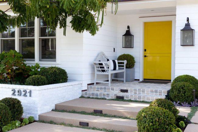 Традиционный экстерьер частного дома с особенностью в виде глянцевой пластиковой входной двери насыщенного желтого цвета с надежным замком