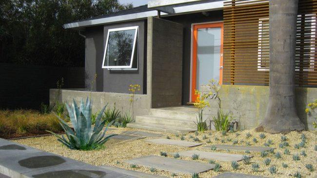Современный экстерьер дома с пластиковыми входными дверями, оснащенными стеклопакетом с полупрозрачным стеклом