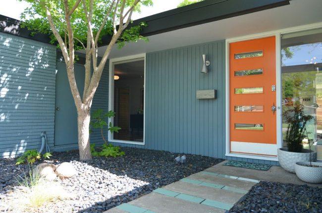 Яркая оранжевая пластиковая дверь – изюминка экстерьера частного дома, сочетающаяся с общим лаконичным дизайном