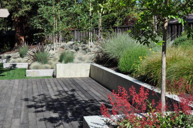 Низкая бетонная стенка, украшающая ландшафтный дизайн дворика
