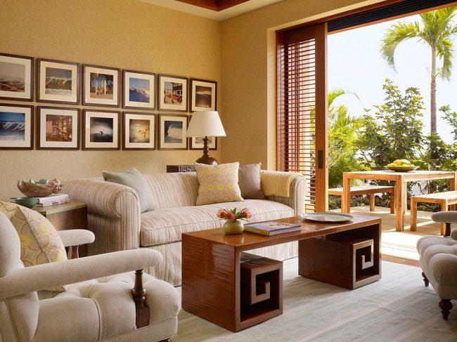 Интерьер комнаты выполнен в светлых бежевых и коричневых тонах. Фотографии вручную наклеены на белую бумагу и обрамлены темно-коричневыми деревянными рамками