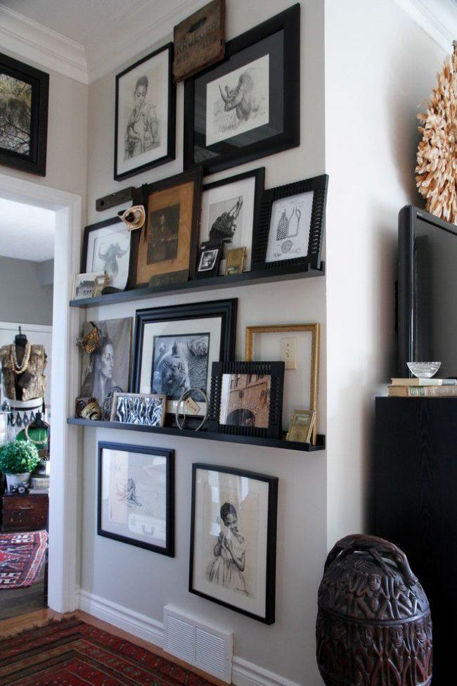 Эклектическая прихожая с авторской графикой в стандартных и оригинальных черных рамках. Некоторые картины весят на стенах, а некоторые из коллекции стоят на полках