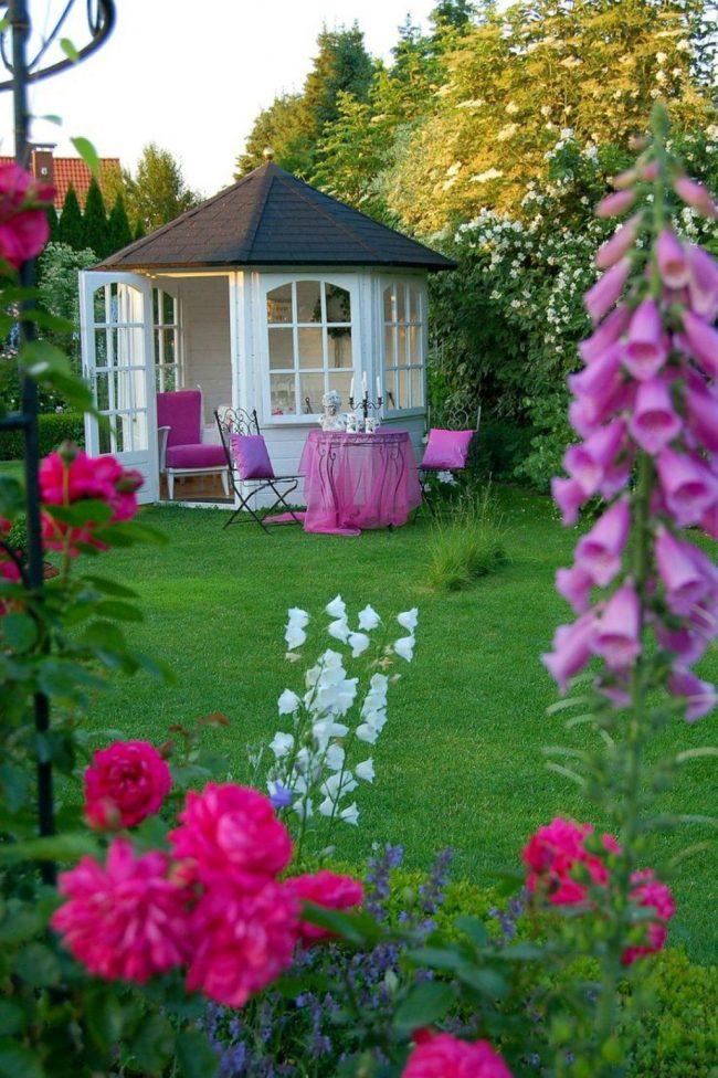 Белая беседка с решеткой в саду