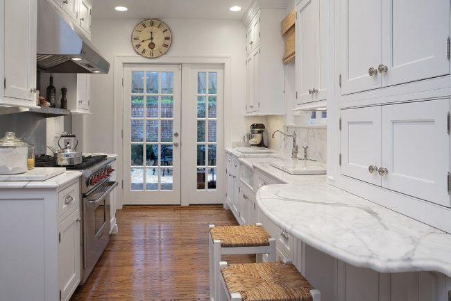 Поверхность кухонного гарнитура из искусственного камня служит обеденным местом. Опора: деревянный фасад гарнитура