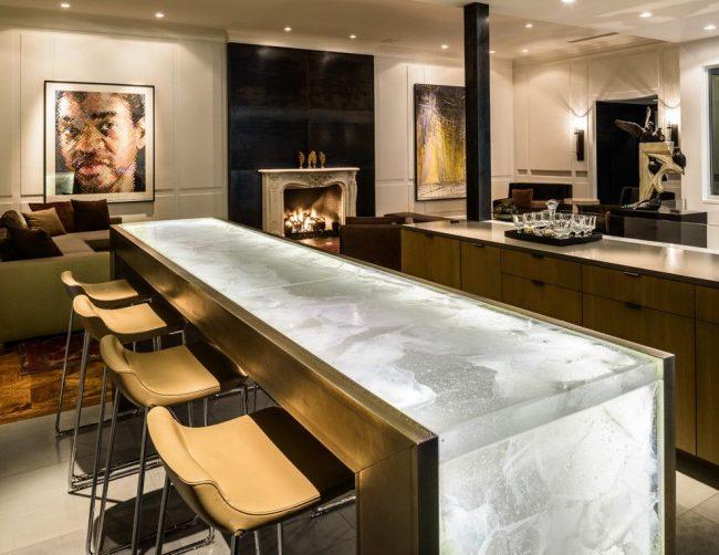 Элегантный дизайн кухни со столом из искусственного камня в сочетании с металлическими деталями, оснащенного встроенной подсветкой