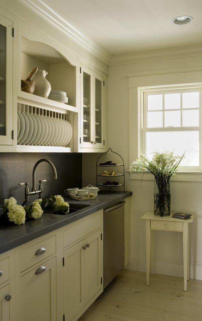 Открытая сушилка для посуды над раковиной на небольшой кухне в светлых тонах