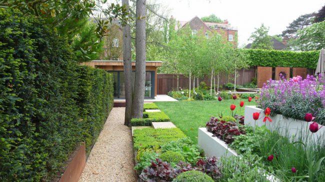 Очень красивый задний двор частного дома с многоярусной цветочной клумбой. Обратите внимание, что гейхера также отлично сочитается с цветущими растениями