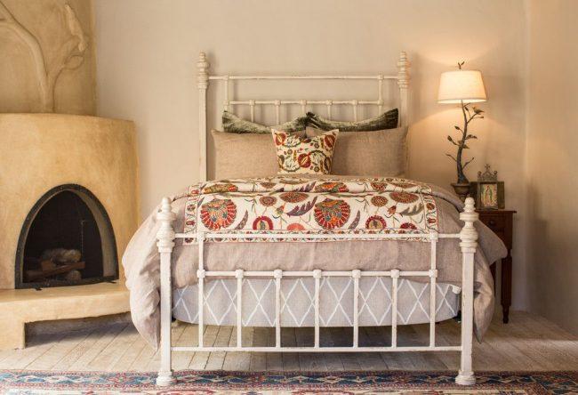 Испанский стиль в интерьере: камин и кованая кровать создают испанский стиль в спальне