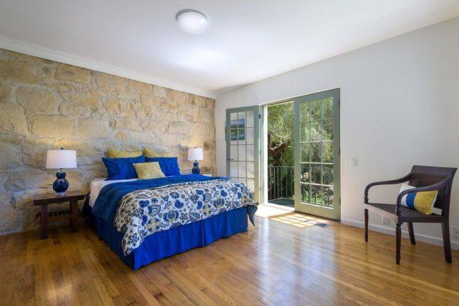 Просторная спальня с каменной стеной у изголовья кровати