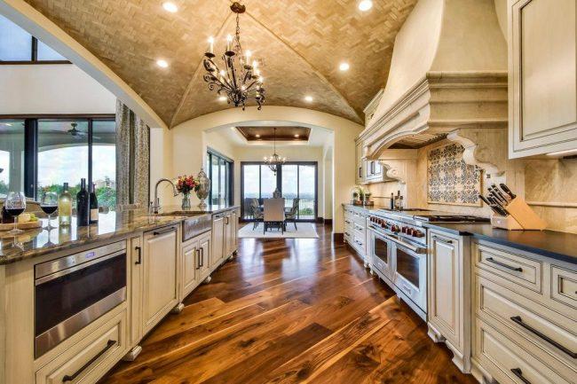 Большая кухня в испанском стиле с кованной люстрой и красивым деревянным полом