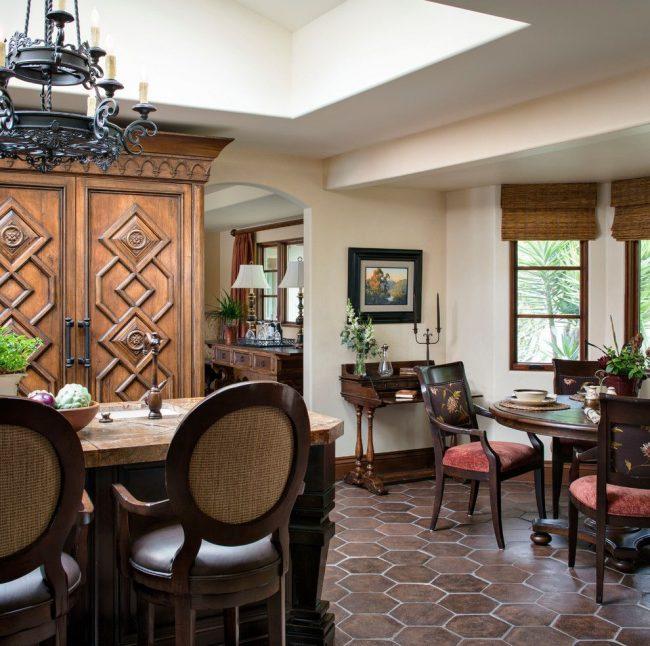 Красивая деревянная мебель и кованая люстра в интерьере испанского стиля