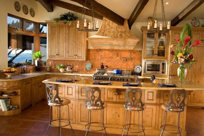 Элементы кованой мебели и оранжевый фартук из кафельной плитки на классической испанской кухне