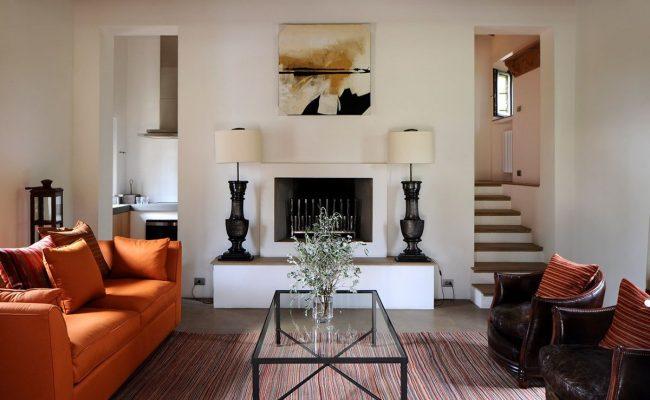 Контраст ярко-оранжевого дивана и коричневых кресел присущи средиземноморскому стилю