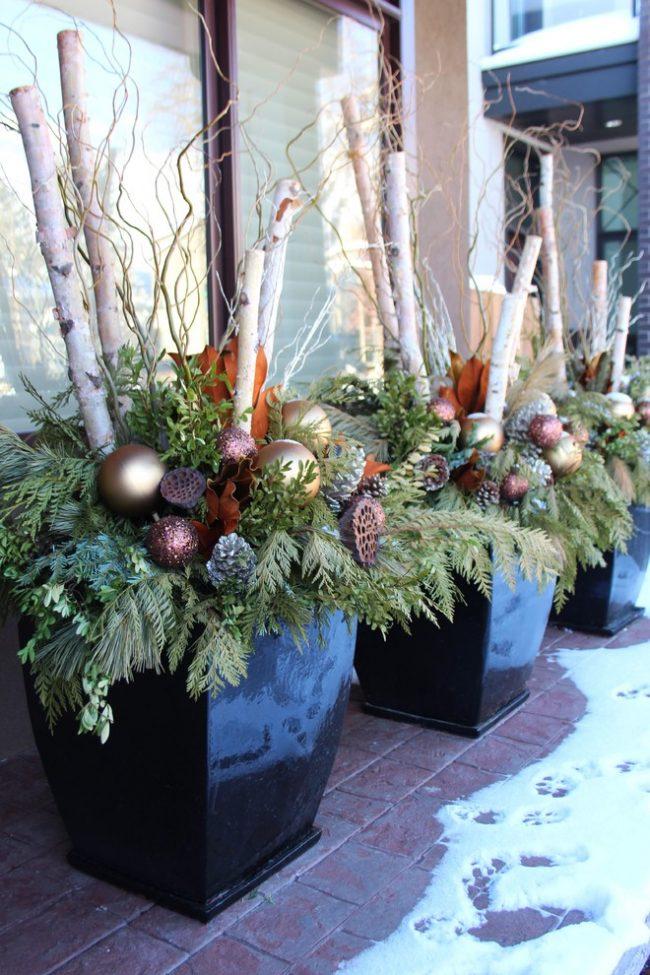 Прекрасные садовые вазы, украшенные хвойными ветками и новогодними игрушками