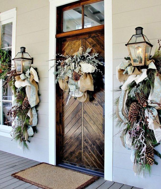 Дверь дома, украшенная традиционным рождественским венком из хвойных ветвей, смотрится очень красиво