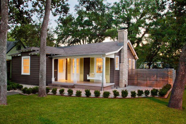 Одноэтажный деревянный дом с качелей на террасе
