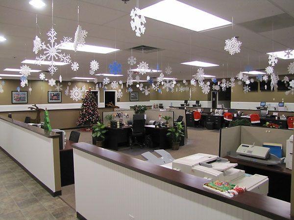 Большой офис, украшенный бумажными снежинками