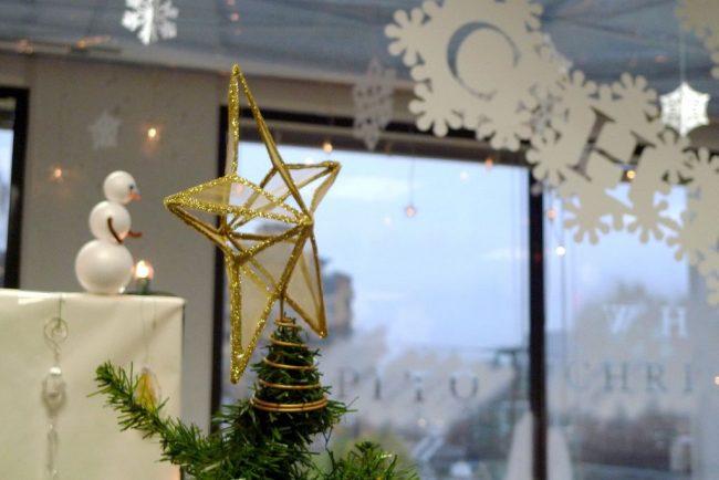 Светлый офис украшенный бумажной новогодней надписью