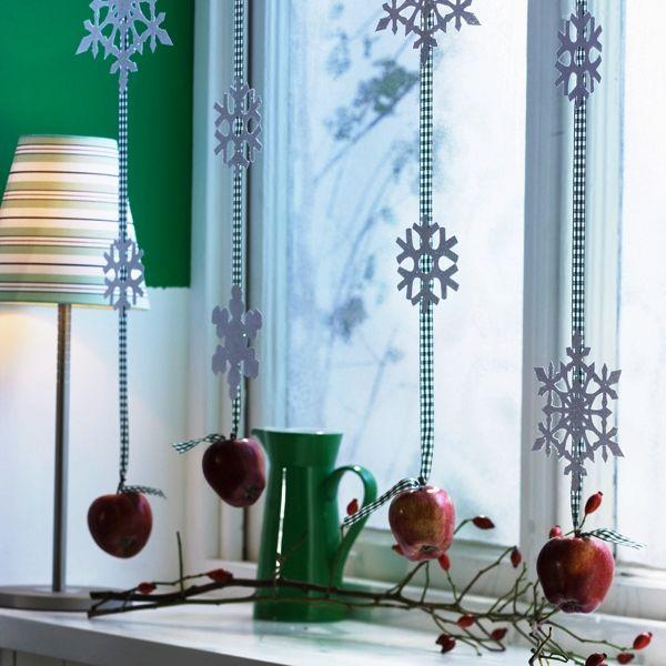Бумажные снежинки и яблоки на лентах красиво и оригинально украсят зону окна