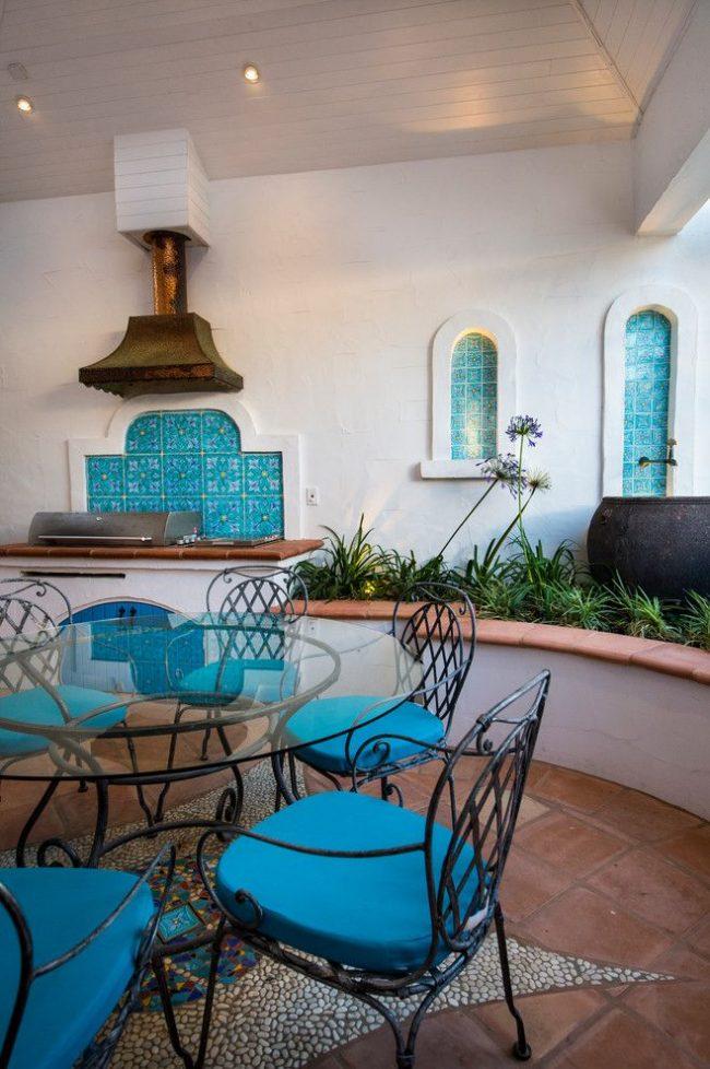 Яркую керамическую плитка бирюзового цвета дополняют сиденья стульев