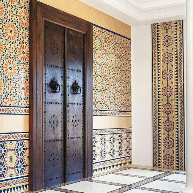 Восточный интерьер с массивными деревянными дверями и марокканской плиткой на стенах и на полу