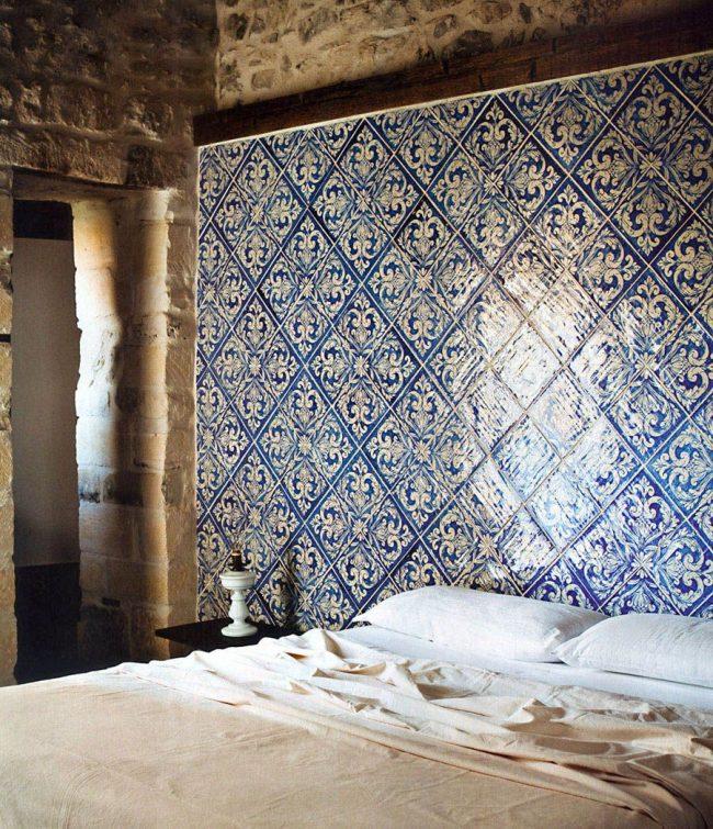 Изголовье кровати из керамической плитки в сочетании с каменными стенами выглядит очень необычно