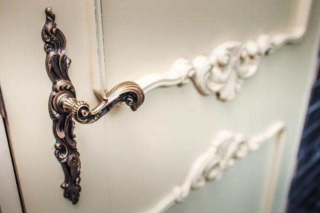 Роскошная межкомнатная дверь в классическом стиле с красивой металлической нажимной ручкой с замком