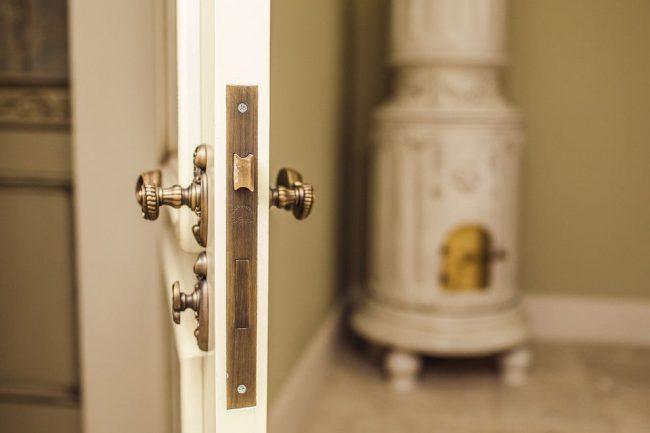 Светлая деревянная дверь с красивой дверной ручкой под бронзу