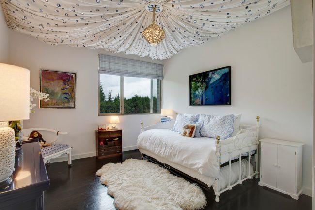 Красивый натяжной тканевый потолок в светлой спальне
